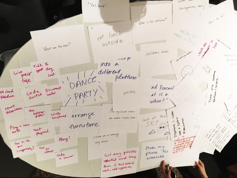 A table with notes full of handwritten examples of oblique strategies