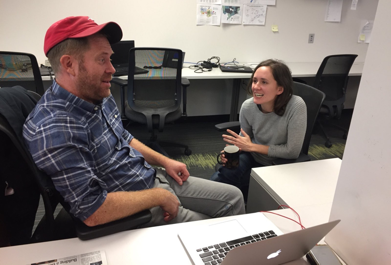 Two people at a desk, talking in front of a laptop