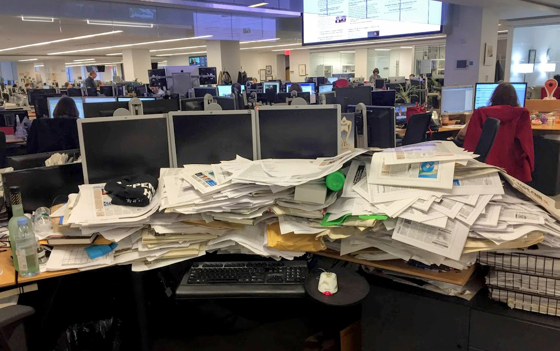 A newsroom desk piled with papers.