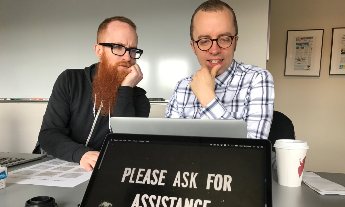 photo of two web designers looking at a laptop in bemusement
